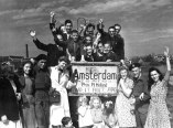 "A group of civilians and soldiers pose behind a sign that proclaims: ""Amsterdam, North Holland. This is May 10th. And it ain't 1940."""