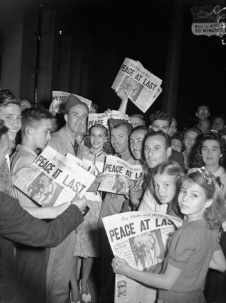 "Children, family members, and a couple of soldiers read the August 14th edition of The Globe and Mail declaring ""Peace at Last"" on the front page."