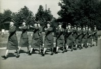 Female Nursing Corps march together in their uniforms.