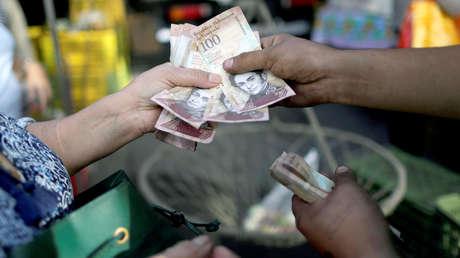 Un cajero recibe billetes bolívares venezolanos de un cliente en un mercado callejero en el centro de Caracas, Venezuela.