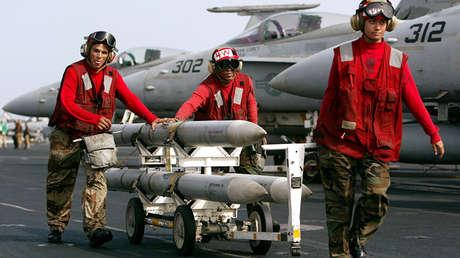Militares transportan misiles AIM-120 AMRAAM en la cubierta del portaviones USS Kitty Hawk, el 10 de marzo de 2003.