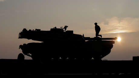 Los soldados estadounidenses preparan un tanque M1 Abrams para descargar de un tren en la Base Aérea de Mihail Kogalniceanu, Rumania.