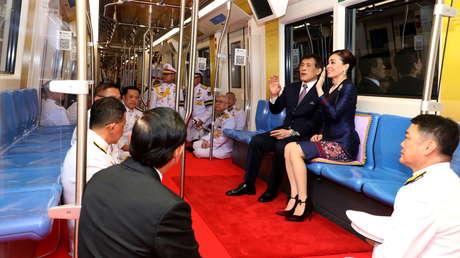 FOTOS: El rey de Tailandia y su esposa viajan en un vagón de metro acompañados solamente por funcionarios y periodistas postrados a sus pies