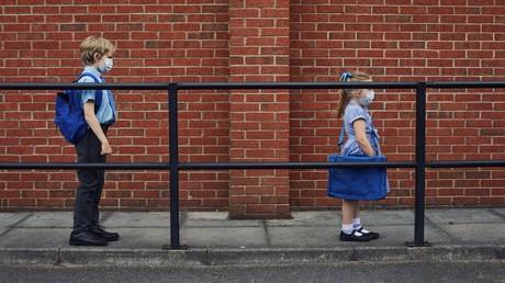 Zwei Kinder, die mit Gesichtsmasken zur Schule gehen und wegen