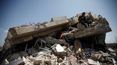 A police trooper sits on the wreckage of a house hit by air strikes on an outskirt of Sanaa, Yemen May 10, 2018.  © Mohamed al-Sayaghi