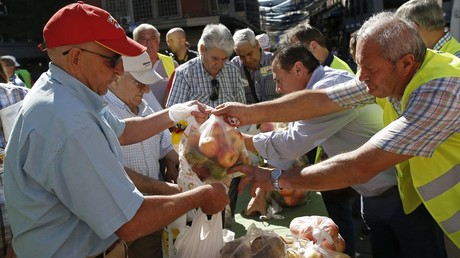 People take fruits and vegetables given away in central Madrid by Spanish farmers to protest against Russia's ban on vegetables, meat, fish, milk and dairy imports from the European Union © Andrea Comas