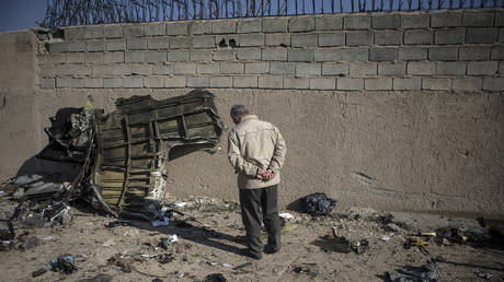 A man stands near a piece of debris of a Boeing 737 Ukrainian passenger plane at the air crash site in Parand district, southern Tehran, Iran, on Jan. 8, 2020. © Global Look Press/Xinhua/Ahmad Halabisaz