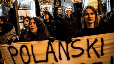 "FILE FOTO: Demonstrators hold banners during a protest against French-Polish film director Roman Polanski outside the ""Champo"" cinema hall in Paris on November 12, 2019"