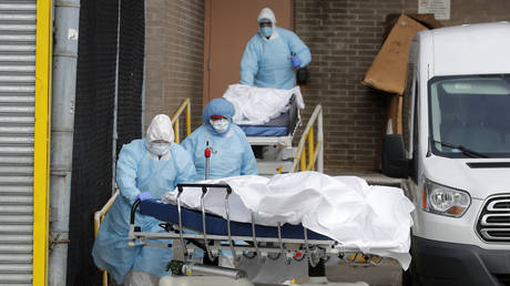 Healthcare workers wheel the bodies of deceased people from the Wyckoff Heights Medical Center, New York on April 2, 2020.