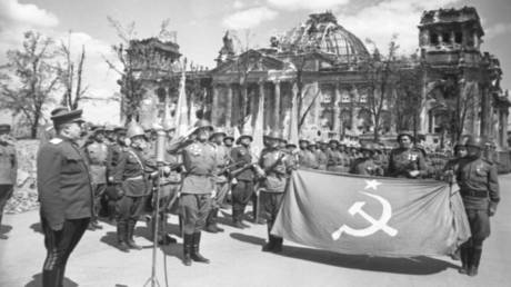 Soviet soldiers pose in front of the Reichstag building, days after the Battle of Berlin. © Sputnik / Oleg Knorring