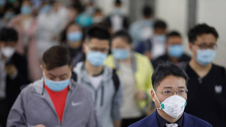 People wearing face masks walk inside a subway station during morning rush hour in Beijing