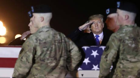 US President Donald Trump salutes a casket with the remains of Chief Warrant Officer David Knadle, who was killed in a helicopter crash in Afghanistan, at Dover Air Force Base, Delaware, November 21, 2019.