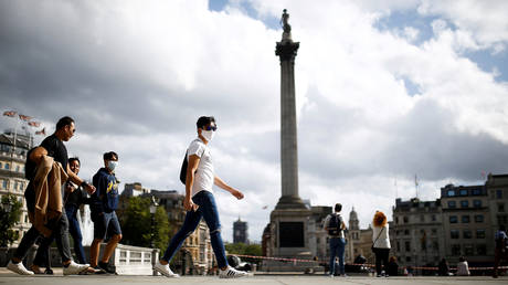People wearing face masks walk through Trafalgar Square in London, UK. © REUTERS/Henry Nicholls