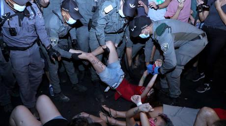 Police officers detain a protester during a demonstration against Israeli PM Benjamin Netanyahu in Jerusalem, September 6, 2020