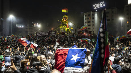 Demonstrators supporting the reform of the Chilean constitution celebrate while waiting for the referendum official results at Plaza Italia square in Santiago on October 25, 2020.