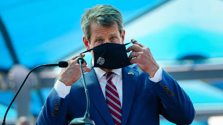 FILE PHOTO: Georgia Governor Brian Kemp puts on a mask after speaking at a press conference on August 10, 2020.