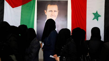 FILE PHOTO: Women stand as they wait their turn to cast the votes inside a polling station during the parliamentary elections in Douma, in the eastern suburbs of Damascus, Syria July 19, 2020