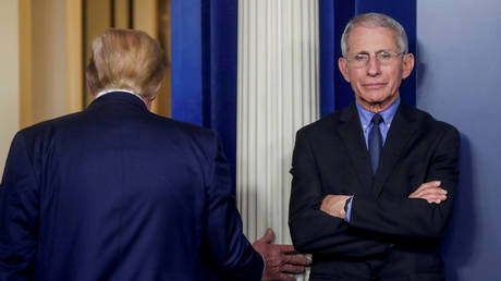 Dr. Anthony Fauci is shown at a White House Covid-19 briefing in March as President Donald Trump is walking away.