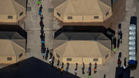 FILE PHOTO: Migrant children are led by staff in single file between tents at a detention facility next to the Mexican border in Tornillo, Texas.