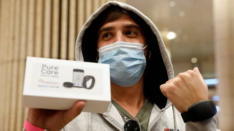 A traveler shows off an electronic bracelet as Israel introduces them to enforce Covid-19 quarantines, at Ben Gurion international airport near Tel Aviv, Israel March 1, 2021.
