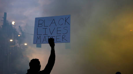 """FILE PHOTO: A person holds a """"Black Lives Matter"""" sign as a heavy cloud of tear gas and smoke rises after being deployed by Seattle police as protesters rally against police brutality and the death in Minneapolis police custody of George Floyd."""