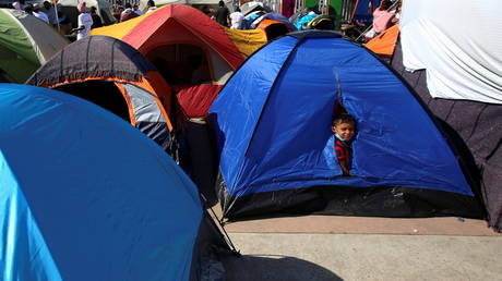 A child looks out from a tent next to other migrants from Central America who are camping outside the El Chaparral border crossing, hoping to cross and request asylum in the U.S. , in Tijuana, Mexico February 27, 2021. © REUTERS/Jorge Duenes
