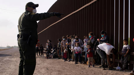 A US Border Patrol agent instructs asylum-seeking migrants as they line up along the border wall after crossing the Rio Grande river into the United States from Mexico on a raft, in Penitas, Texas, US, March 17, 2021