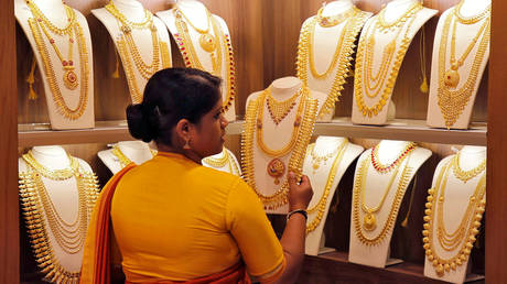 A saleswoman picks gold necklaces to show it to a customer inside a jewellery showroom in India