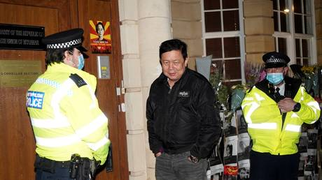Myanmar's Ambassador to the United Kingdom, Kyaw Zwar Minn, stands with police officers locked outside the Myanmar Embassy in London on April 7, 2021.