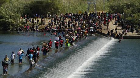 FILE PHOTO. Haitian migrants use a dam to cross to and from the United States from Mexico in Del Rio, Texas. ©AP Photo / Eric Gay