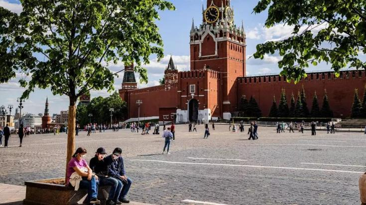 A picture taken on May 25, 2021 shows people wearing protective face masks against the coronavirus, Covid-19, as they rest in Red Square in Moscow