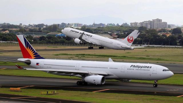 A Japan Airlines Boeing 767-300ER plane takes off as a Philippine Airlines Airbus A330-300 plane taxis on the runway of the Ninoy Aquino International Airport (NAIA) terminal 1 in Pasay city, metro Manila, Philippines January 11, 2018.