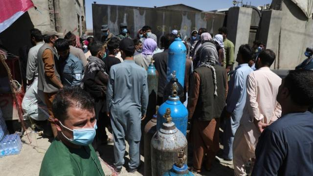 Men wait outside a privately owned oxygen factory to get their oxygen cylinders refilled, in Kabul, Afghanistan on June 19, 2021.
