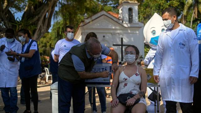 Brazil's Health Minister Marcelo Queiroga (L) gives a dose of AstraZeneca/Oxford vaccine during the first day of a mass vaccination campaign in Rio de Janeiro, Brazil on June 20, 2021.