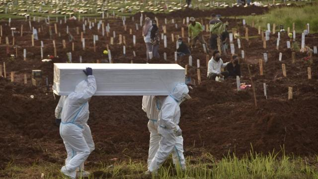 Gravediggers carry a coffin of a Covid-19 victim for burial at a cemetary in Bekasi on July 2, 2021, as infections surge to record levels in Southeast Asia's worst-hit nation.