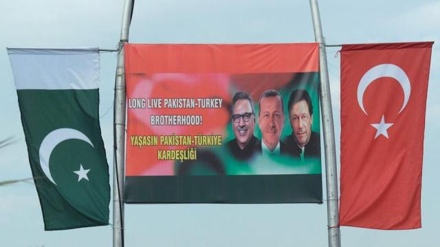 Flags of both countries are seen on poles next to a sign showing Pakistani leader Arif Alvi (L), Turkish leader Recep Tayyip Erdogan (C) and Pakistani PM Imran Khan, in Islamabad, on Feb 13, 2020.