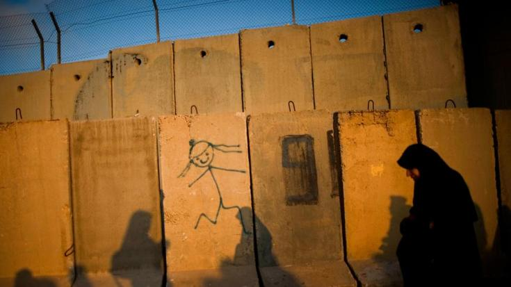FILE PHOTO: A Palestinian woman crosses the Kalandia checkpoint between Jerusalem and the occupied West Bank city of Ramallah, on August 13, 2010.