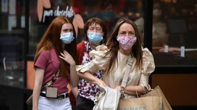 Shoppers wearing protective face coverings to combat the spread of the coronavirus, walk along Oxford Street in central London on July 5, 2021.