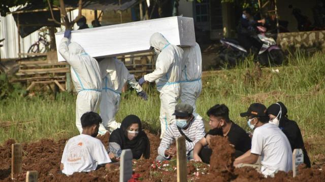 A family gather to grieve at a grave as gravediggers prepare to bury another Covid-19 victim at a cemetary in Bekasi, Indonesia on July 2, 2021.