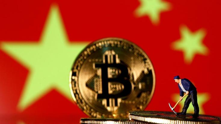 A small toy figurine on representations of the Bitcoin virtual currency displayed in front of an image of China's flag, on April 9, 2019