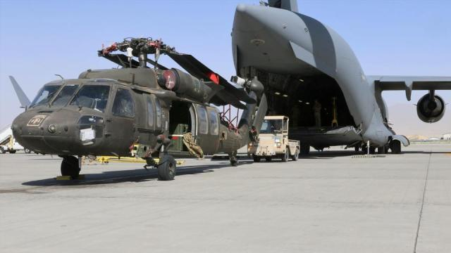 Aerial porters work with maintainers to load a UH-60L Blackhawk helicopter into a US Air Force C-17 Globemaster III during the withdrawal of American forces in Afghanistan, June 16, 2021.