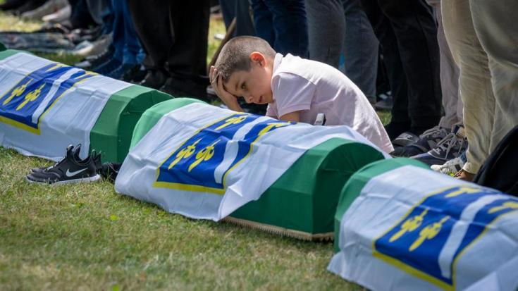 A boy reacts as mourners prepare for the funeral of newly identified victims at the memorial cemetery in Potocari near Srebrenica, Bosnia, on July 11, 2021.