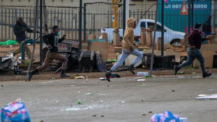A metro officer dressed in plainclothes, fires a rubber bullets forcing looters to disperse at a shopping centre in Soweto, Johannesburg on July 13, 2021.