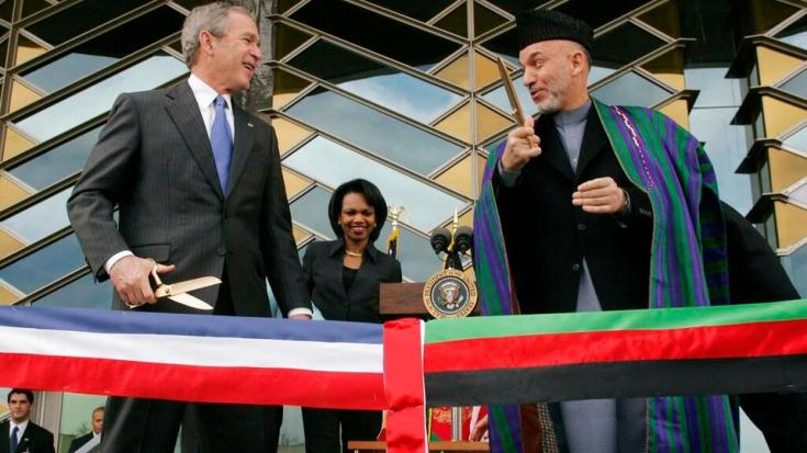 In this March 1, 2006 file photo, US President George W. Bush, left and Afghan President Hamid Karzai get ready to cut a ribbon to officially open the US Embassy in Kabul, Afghanistan.