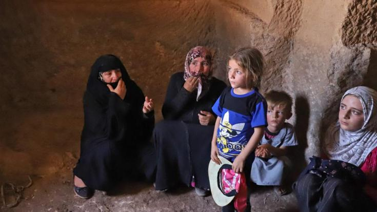 Survivers of a reported shelling by regime forces, huddle inside a house in the village of Serja, in the southern part of Syria's Idlib province, on July 17, 2021.
