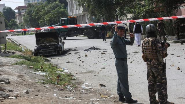 Afghan security personnel stand guard near a charred vehicle from which rockets were fired that landed near the Afghan presidential palace in Kabul on July 20, 2021.