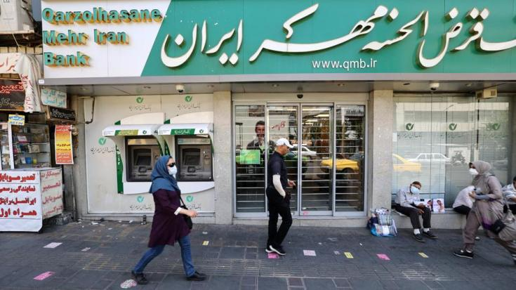 An Iranian woman wearing a protective face mask walks past a shuttered Bank Mehr branch in downtown Tehran on July 20, 2021.