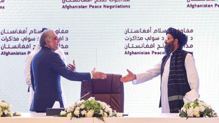 (L to R) Head of Afghanistan's High Council for National Reconciliation Abdullah Abdullah prepares to shake hands with leader of Taliban negotiating team Mullah Abdul Ghani Baradar, Doha, July 18, 2021.