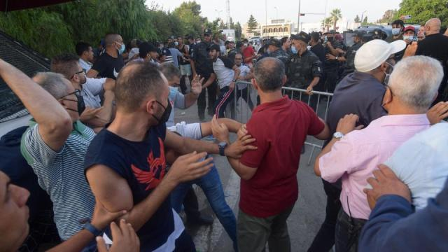Clashes erupt between supporters of Tunisian president and Ennahda party deputies in front of parliament which was cordoned-off by military in capital Tunis on July 26, 2021.