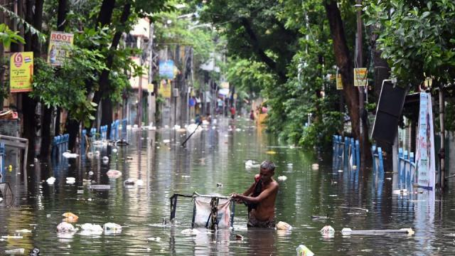 A man pushes his tricycle van through floodwaters following rain in Kolkata, July 30, 2021.